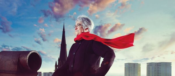 Female volunteer in her 60s, in superhero pose with red scarf blowing in the wind