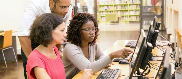 Two women are using computers in the library, one male teacher observes what they are doing.