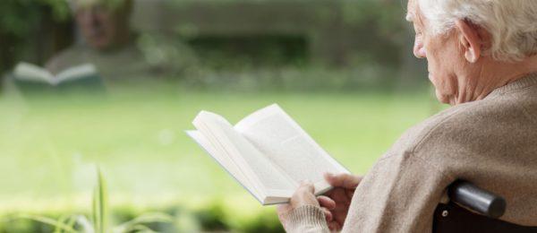 Senior man sat reading a book in his wheelchair