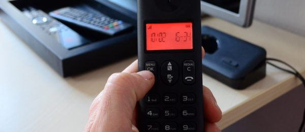 Phone handset from a home landline. Black handset with red display saying 10/02 16:34