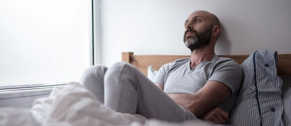 Bald middle aged man with a beard, lying on a bed with his knees up and arms folded, staring out of the window looking fed up