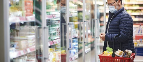 A middle aged man is shopping in a supermarket wearing a mask holding a basket