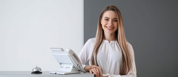 young woman stands to side of reception desk smiling