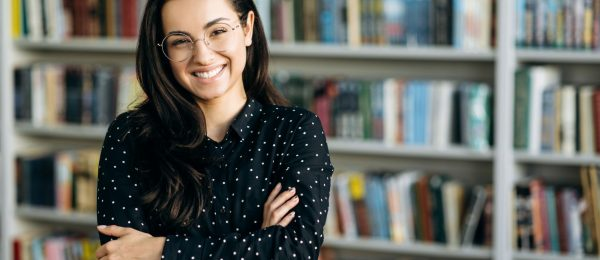 A young woman stood in front of library book shelves smiling.