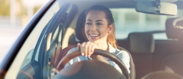 A young woman smiles whilst driving a car.