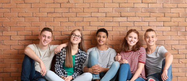 A photo o3 teenage girls and 2 teenage boys sat on the floor smiling
