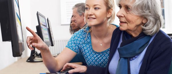 A young woman helps an older woman, both are seated in front of a computer.