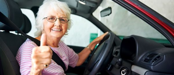 Older woman sat in driving seat of red car with her thumb up